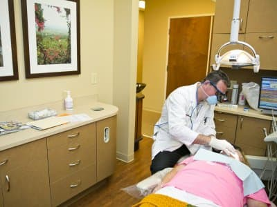 a dentist installs a dental implant on a patient